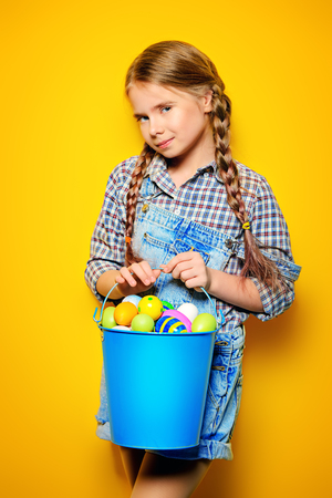 Children's fashion. Cute nine year old girl with long blonde hair is posing in summer clothes with a bucket of easter eggs. Studio shot.