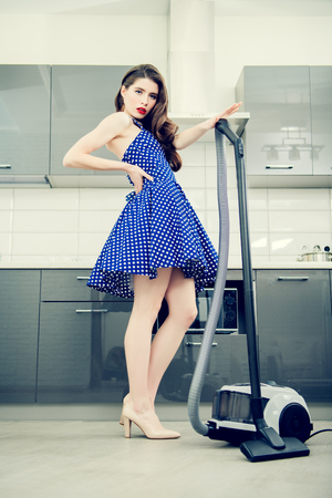 Beautiful young housewife wearing in a blue dress with white dots in the kitchen. Pin-up style. Fashion home shot. Full length portrait.