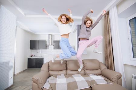 Due amiche in abiti domestici che saltano sul divano.