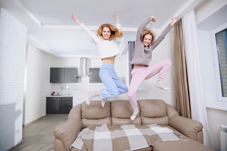 Two girlfriends in home clothes jumping on the couch. Фото со стока