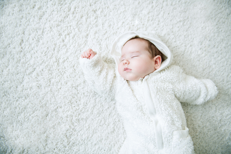 A portrait of a beautiful baby lying in the bed. Family, parenthood. Goods for newborns. Stockfoto