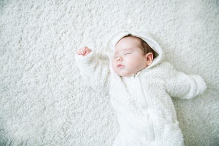 Ein Porträt eines schönen Babys, das im Bett liegt. Familie, Elternschaft. Waren für Neugeborene.