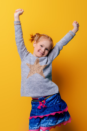 Kid's fashion. Portrait of a cute six year old girl wearing knitted clothes posing over bright yellow background. Spring, winter fashion. Happy child girl. Фото со стока
