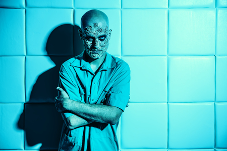 A portrait of a sick scientist after a failed experiment in the blue light. desperation, hopelessness. Horror, halloween. Stock Photo