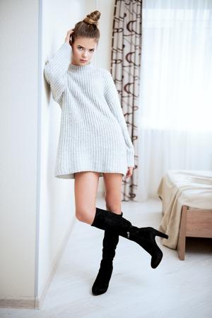 Retrato de una linda chica adolescente se apoya en la pared de la habitación. Belleza, moda.