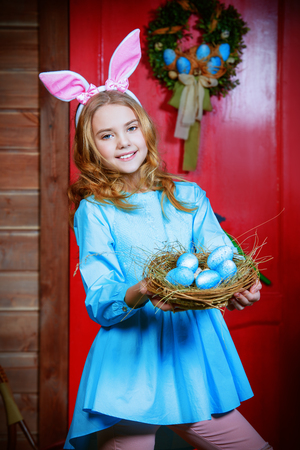 Happy little girl with painted eggs is standing on the porch of a wooden house. Easter holidays.