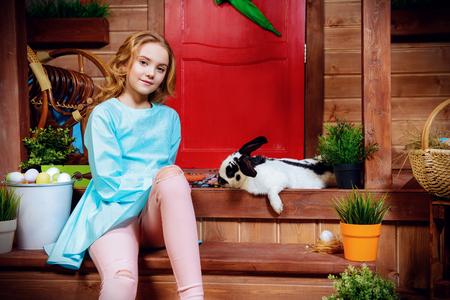 Niña feliz con conejito sentado en el porche cerca de la casa de madera. Pascua vacaciones. Estilo rural, decoración de pascua. Foto de archivo