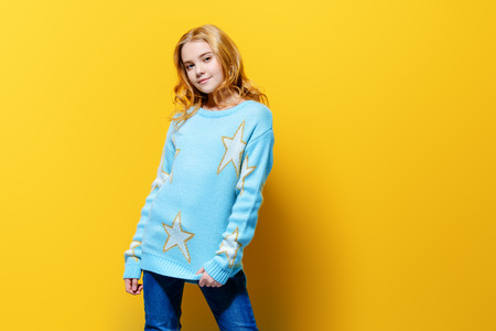 Pretty nine year old girl poses over yellow background and smiling. Kid's fashion. Spring style.