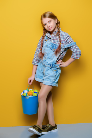 Children's fashion. Cute nine year old girl with long blonde hair posing in summer clothes with a bucket of easter eggs. Studio shot. Full length portrait.