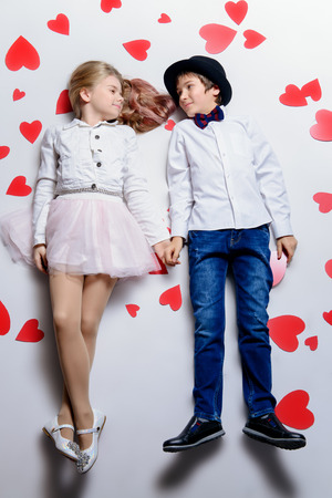 Happy pre-teen boy and girl  are posing surrounded by hearts. Friendship. First love. Valentine's Day.