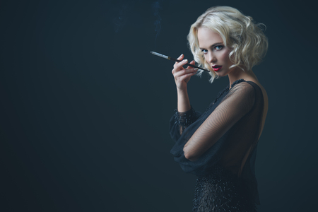 A beautiful blonde lady is smoking a cigarette. Evening dress. Fashion, beauty.