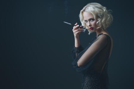 A beautiful blonde lady is smoking a cigarette. Evening dress. Fashion, beauty.