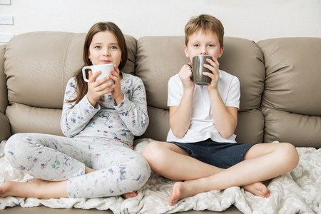 Cute boy and girl are  sitting on the couch with cups.  Fashion home shot. Childhood. Kid's fashion.