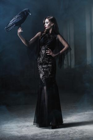 Eine schöne brünette Dame mit einem Raben in Trümmern. Abendkleid. Mode, Schönheit.