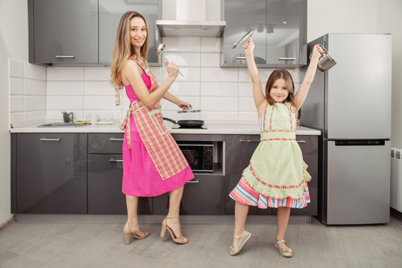 A full length portrait of mother and daughter in aprons with pots in the kitchen.