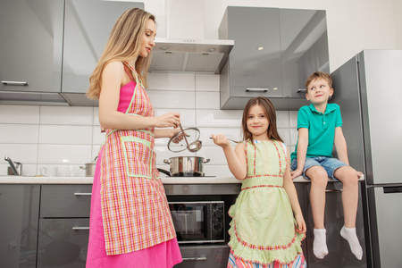 Une jeune femme avec ses enfants prépare un repas dans la cuisine. Shooting à domicile en famille.