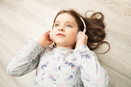 A pretty little girl is lying with headphones on the floor and smiling.  Fashion home shot. Childhood. Kids fashion. Stock Photo