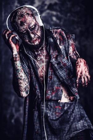 Creepy scary zombie is listening to music with headphones. Halloween. Horror film. Imagens