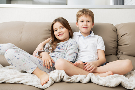 Cute boy and girl are  sitting on the couch.  Fashion home shot. Childhood. Kid's fashion. Stock Photo