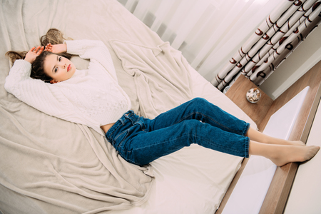 Portrait of a cute girl teenager lying on the bed in the bedroom. Beauty, fashion. Stock Photo
