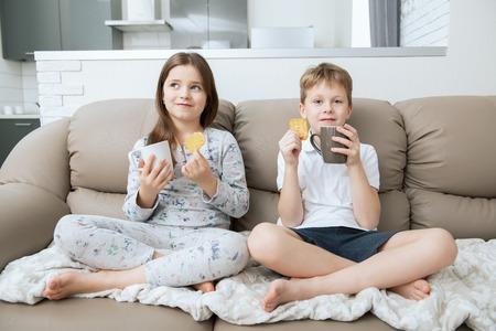 Chico y chica lindos están sentados en el sofá con tazas. Disparo de casa de moda. Infancia. Moda infantil.