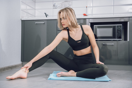 Portrait of a beautiful sexy girl is practicing yoga on the floor in the kitchen at home. Fitness at home, yoga. Stockfoto