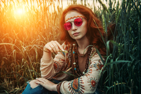 A portrait of a fashion female model sitting on the grass. Contemporary bohemian style. Spirit of freedom. Fashion shot. Bohemian, bo-ho style. Stok Fotoğraf