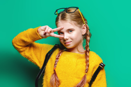 Cute nine year old girl posing in studio in yellow dress over blue background. Children's beauty and fashion.