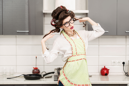 Beautiful young housewife stands in the kitchen. Pin-up style. Fashion home shot.