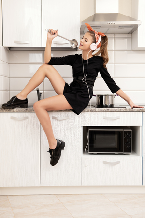 A nice young girl with a headband stands on the background of the kitchen set.