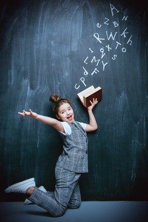 A full length portrait of a cute girl standing with a book over a blackboard. School, education. Stock Photo