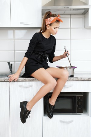 A nice young girl with a headband poses on the background of the kitchen set.