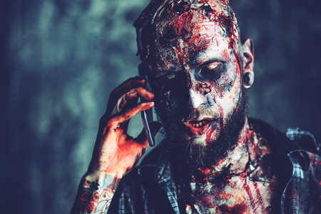 Creepy scary zombie is talking on the mobile phone. Halloween. Horror film.