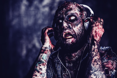 Creepy scary zombie is listening to music with headphones. Halloween. Horror film. Imagens