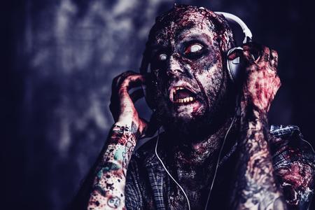 Zombie aterrador espeluznante está escuchando música con auriculares. Víspera de Todos los Santos. Película de terror. Foto de archivo