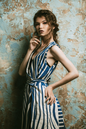 Beautiful attractive girl wearing striped long dress posing in studio. Beauty, fashion. Studio shot. Reklamní fotografie