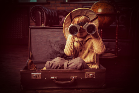 Cute child boy in a travel suitcase playing at home. Childhood. Fantasy, imagination. Stock Photo