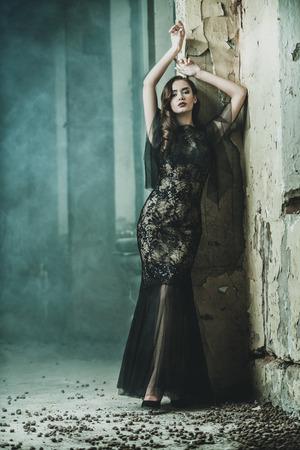 A beautiful brunette lady in ruins. Evening dress. Fashion, beauty.