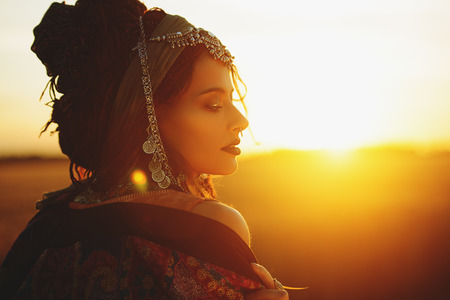 Beau mannequin posant dans des vêtements de style bohème dans les rayons du coucher du soleil. Mode d'extérieur.