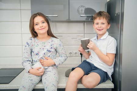 Two cute kids sitting together in the kitchen. Childhood. Kid's fashion.