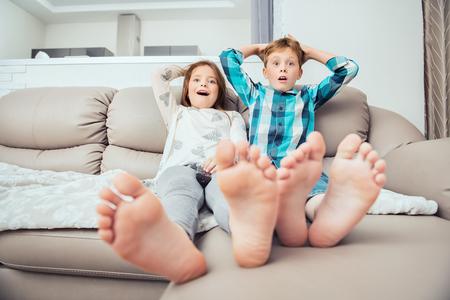 Netter Junge und Mädchen sitzen auf der Couch. Mode nach Hause geschossen. Kindheit. Kindermode.