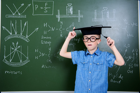 A portrait of a young boy in glasses posing over the blackboard at school. Education, knowledge. 스톡 콘텐츠