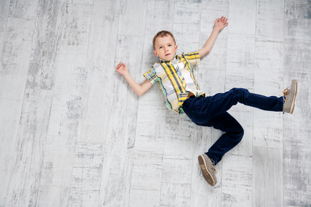 A cheerful boy is lying on the floor. Fashion for kids.