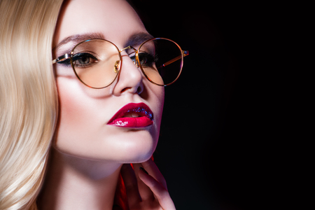 A close up portrait of an elegant lady wearing glasses. Beauty, make-up, style.