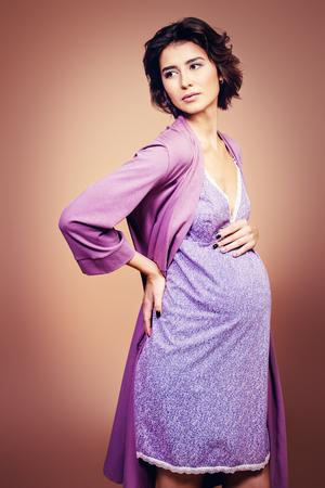Un retrato de una encantadora dama embarazada en estudio. Concepto de moda. Maternidad.