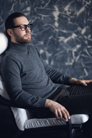 A portrait of a handsome stylish man sitting in the armchair. Fashion for men.