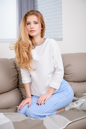 A portrait of an attractive young girl posing at home. Beauty, home clothes.