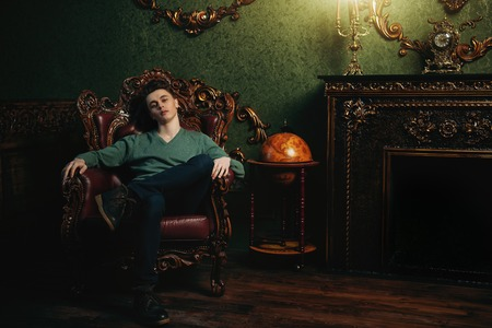 A full length portrait of a handsome young man relaxing in the armchair in the room. Mens beauty, fashion.