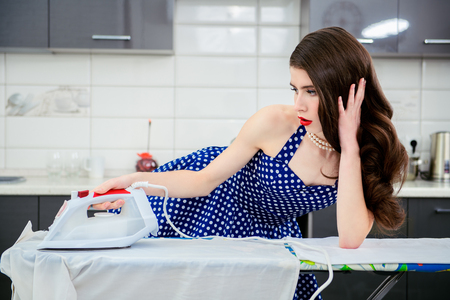 A portrait of an attractive young woman in a blue dress with white dots ironing clothes in the kitchen. Pin-up style. 版權商用圖片