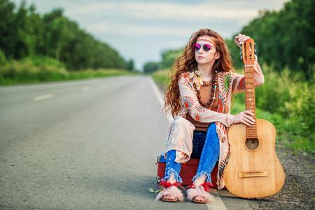 Ragazza che fa l'autostop. Bella ragazza hippie in piedi su un'autostrada e cattura un'auto di passaggio. Spirito di libertà. Colpo di moda. Bohémien, stile bo-ho.